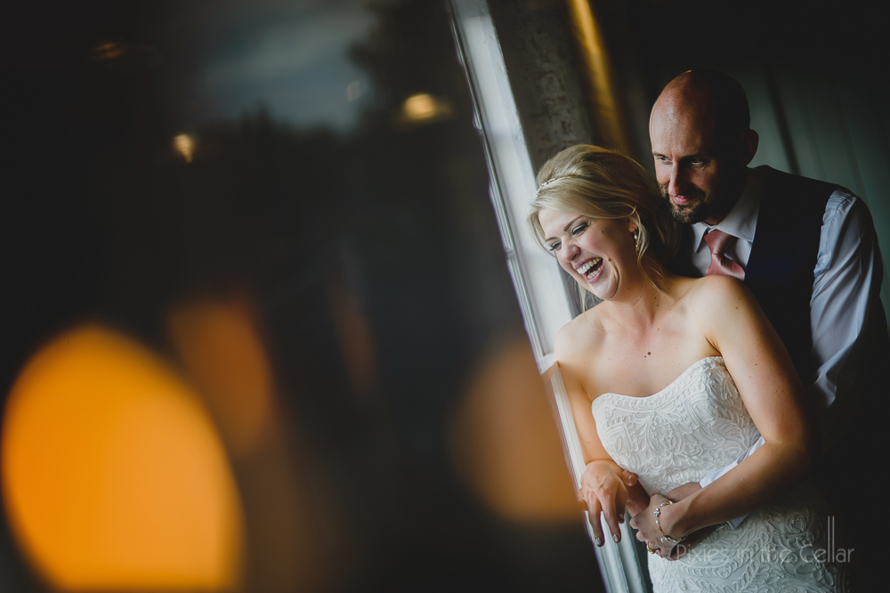 laughing bride in window at west mill