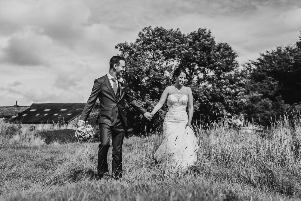 bride groom walking in field at wedding beeston manor