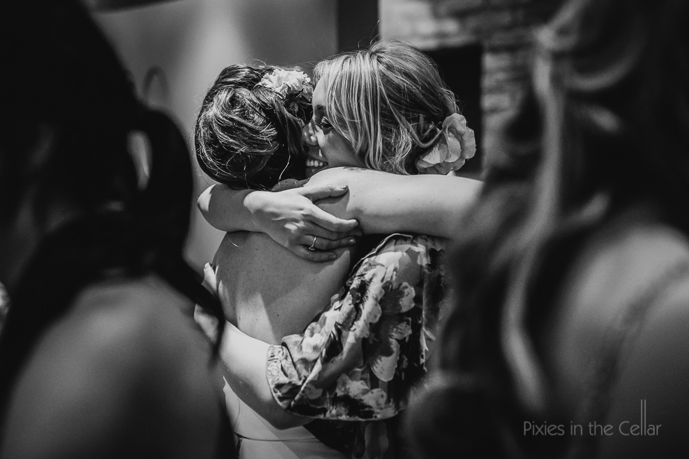 hugs bride and friend black and white photo