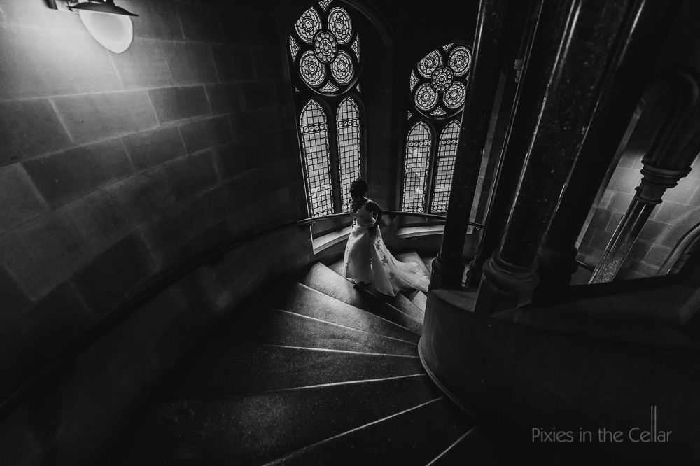 bride arrives spiral stairs moody light