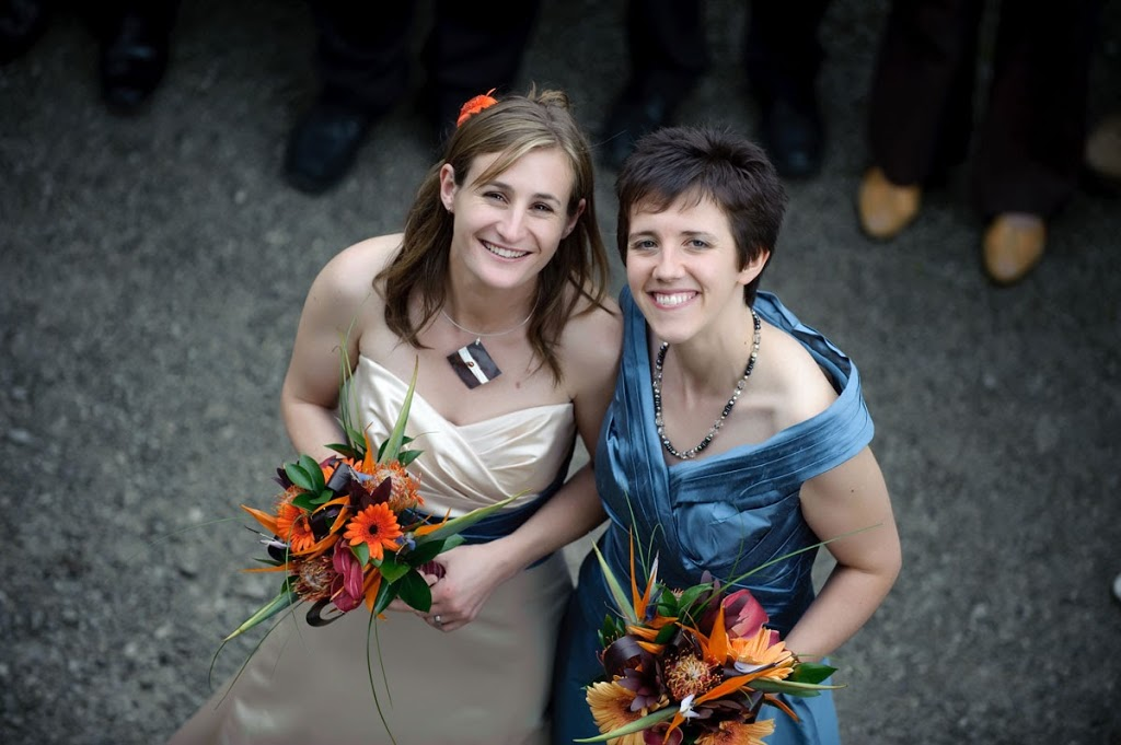 Two brides ivory dress and blue dress orange flowers