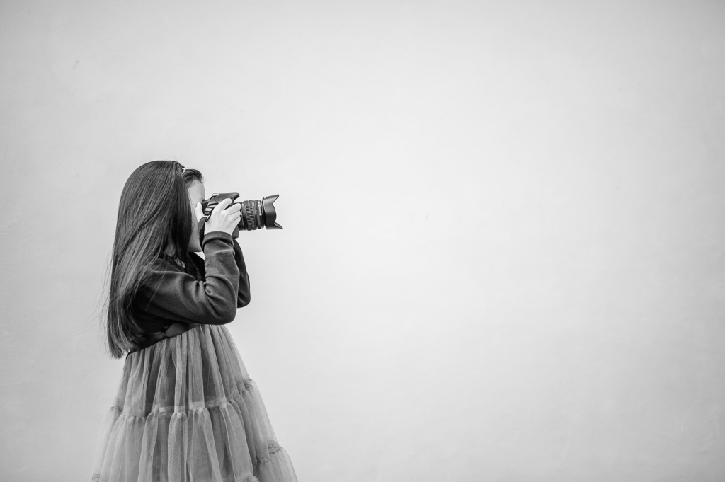 girl and camera from side in black and white