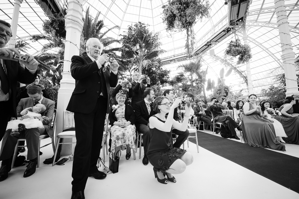 guests taking photos at wedding palm house