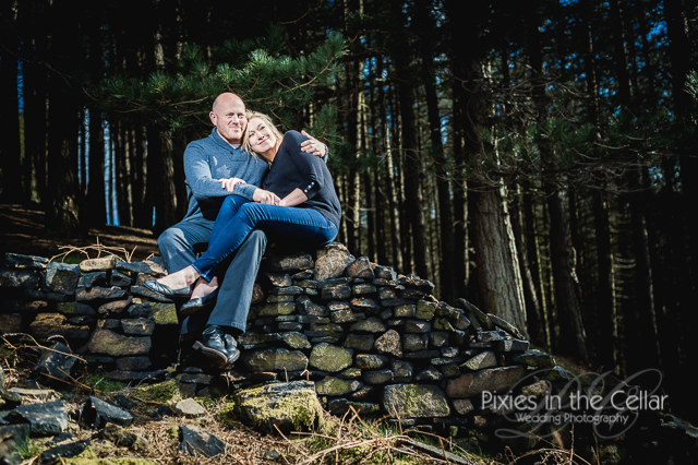 couple sat on wall countryside engagement shoot