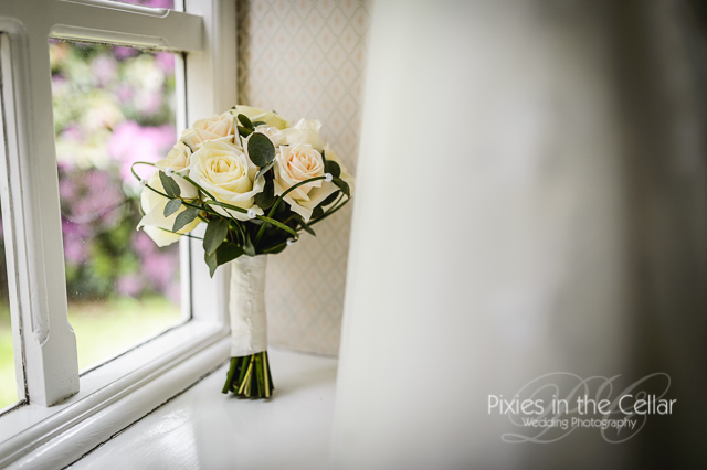 white roses wedding bouquet in window