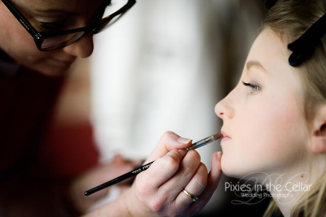 applying lipstick to girl