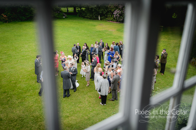 wedding guests on lawn through window