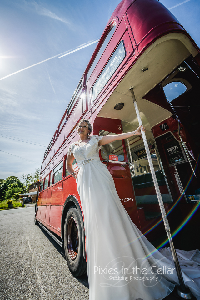 Bride on red bus Manchester wedding