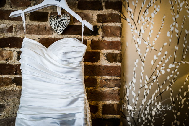 wedding dress on hanger brick wall