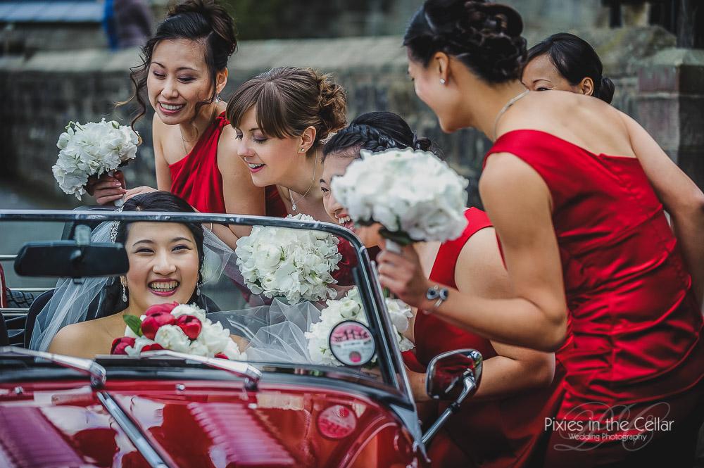 Bride and bridesmaid red morgan car