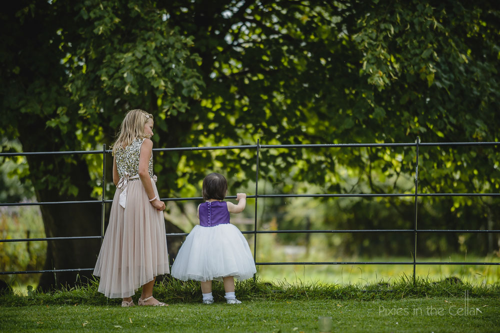 two girls in dresses at fence