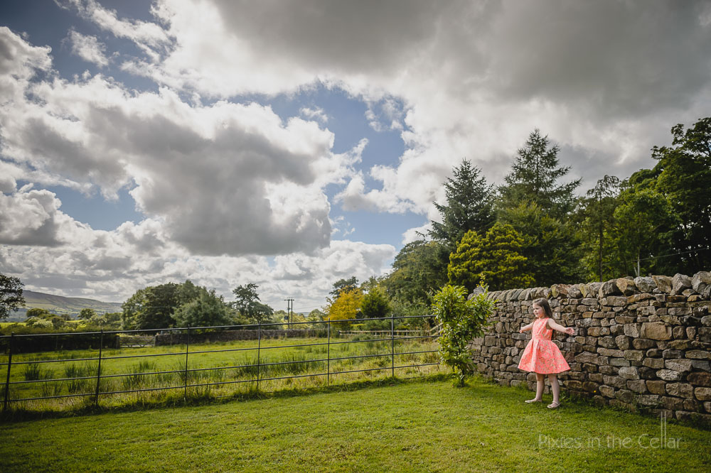 girl in peach dress stone wall