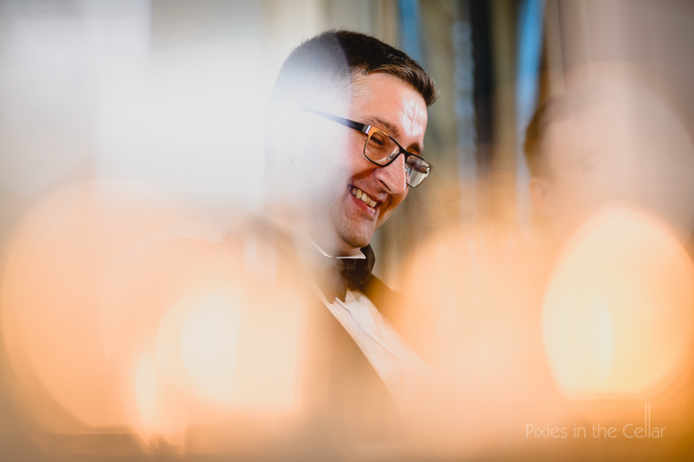 groom smiles candlelight