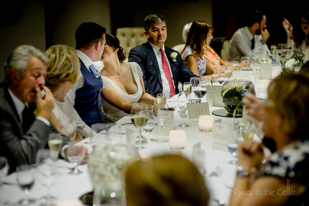 sneaky kiss at wedding table