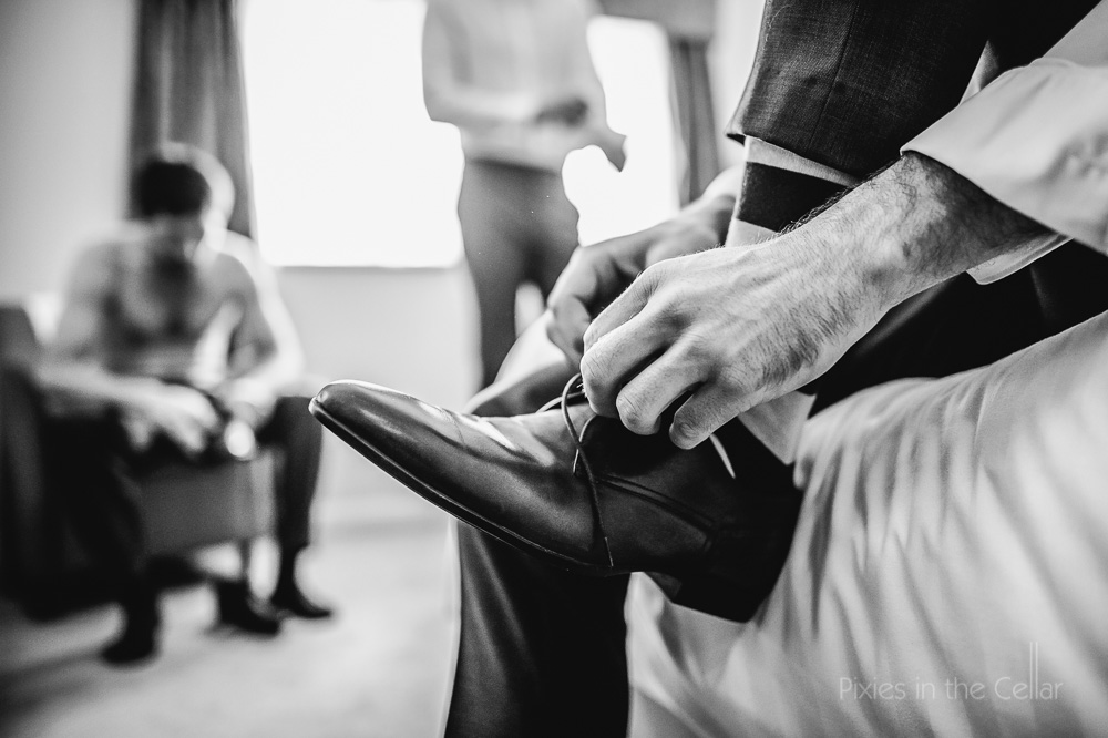 groom tying shoe