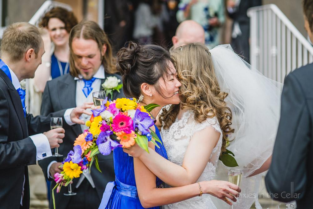 bride hugs bridesmaid in royal blue