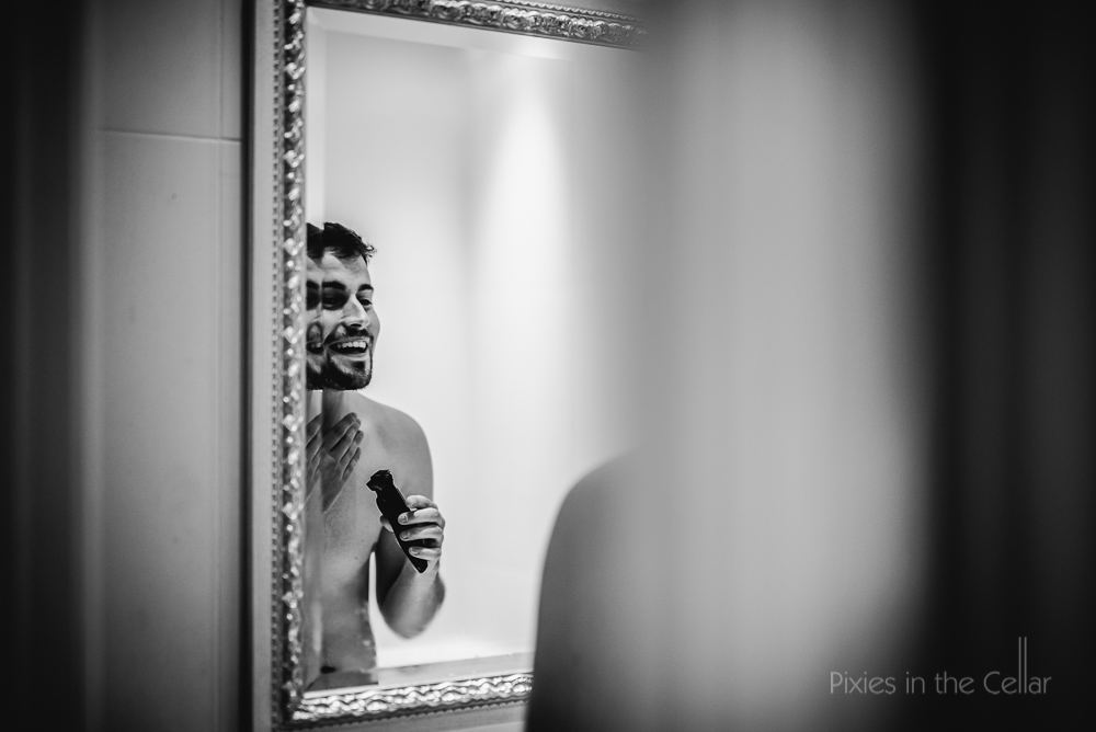 groom shaving in mirror