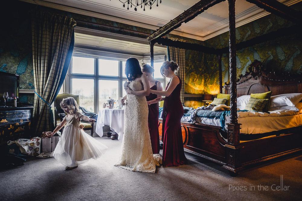 bridesmaids helping bride into wedding dress