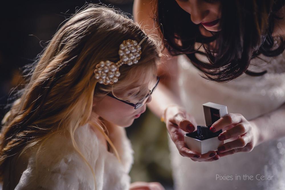 flower girl looking at wedding rings