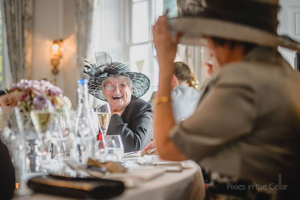 laughing wedding guest with hats