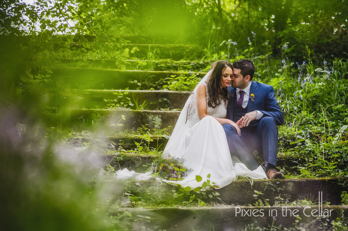 summer wedding couple on steps in lush greenery