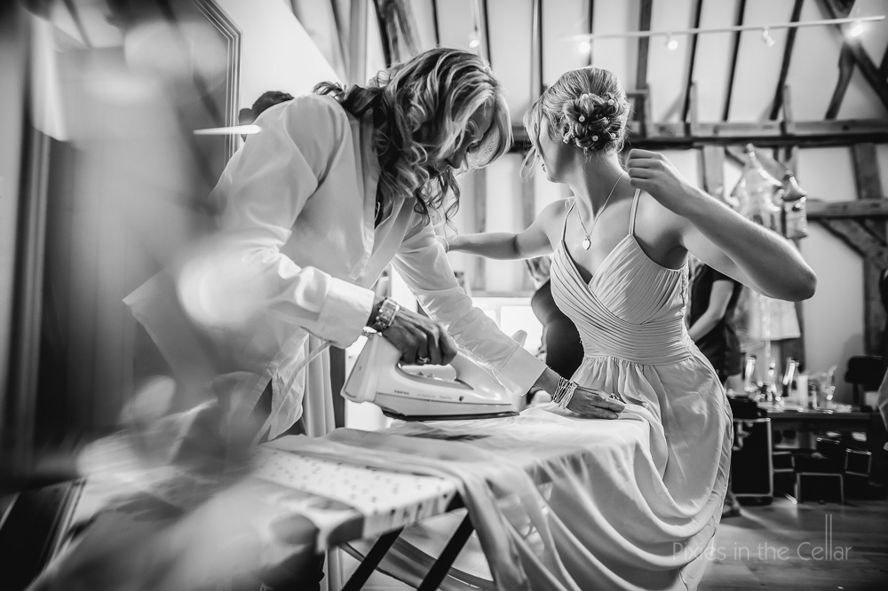 ironing bridesmaid dresses before wedding ceremony at Easton Grange