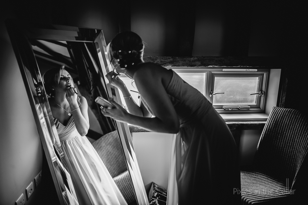 bridesmaid doing make-up in mirror