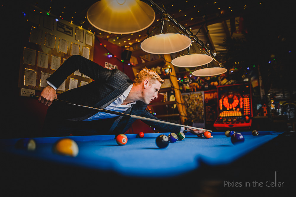 groom playing pool