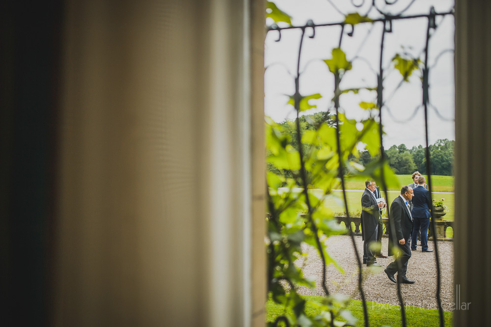 wedding guests through window Cheshire stately home