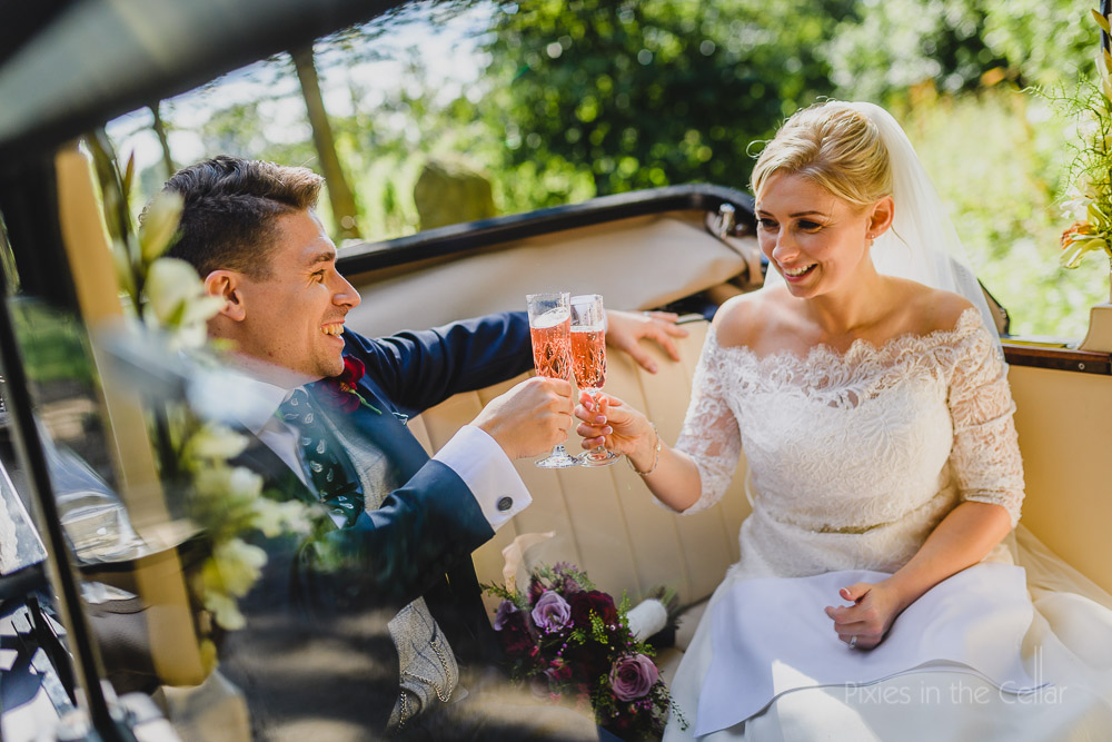 bride and groom champagne in car