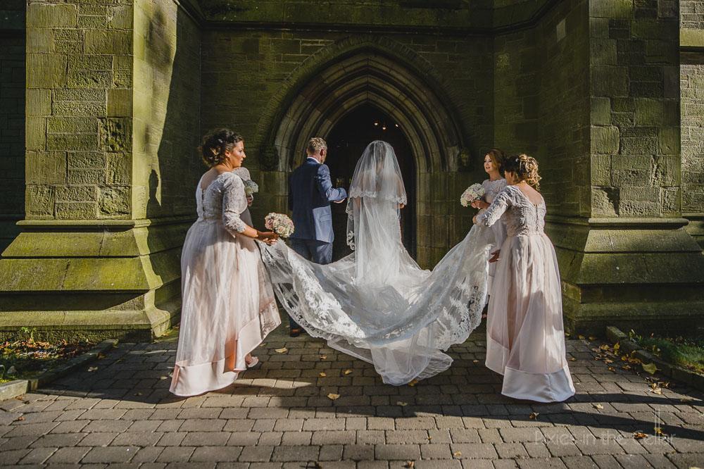 bride and dad entering church with bridesmaids behind