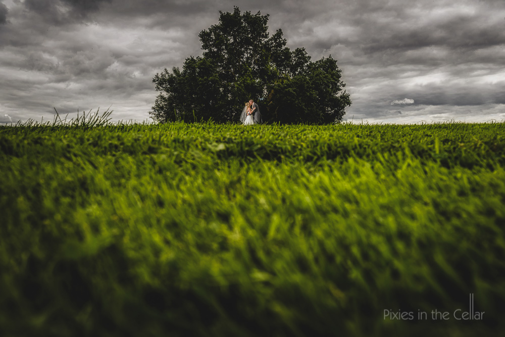 English wedding couple in field moody skies