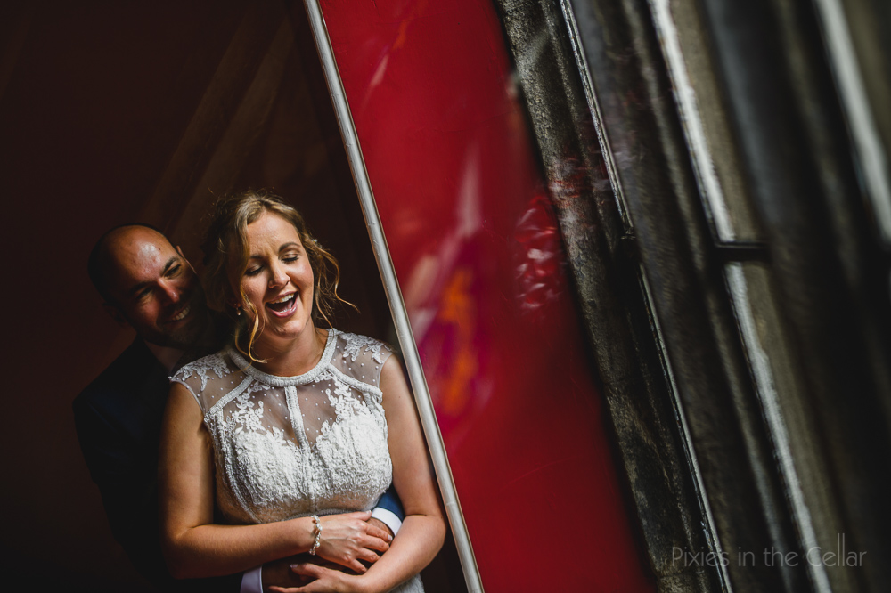 red bride groom laughing at window