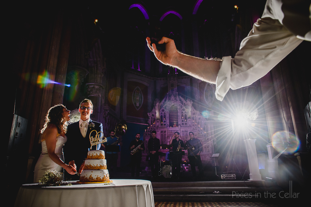 cake cutting decisive moment guests with phone cameras