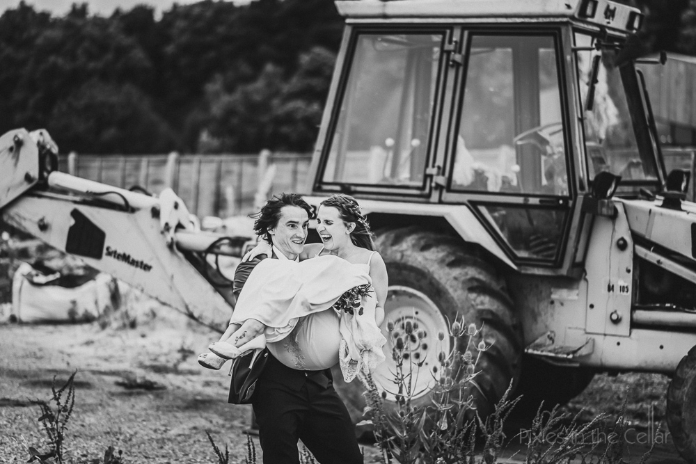 groom carrying bride tractor wedding English wedding